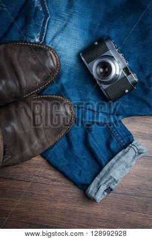 Old Worn Out Brown Leather Shoes With Camera And Jeans On The Floor