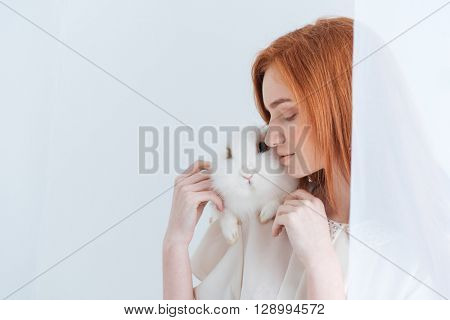 Redhead woman posing with rabbit isolated on a white background poster