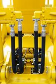 Hydraulic hoses and steel connectors for bulldozers, tractors, excavators and loaders, four, rubber tubes with screws and bolts of yellow machine, construction heavy industry detail poster