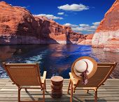 Waves from the boat dissect the lake Powell on the river Colorado. Aft vessels cost two chaise lounges. On a back of one the elegant straw women's hat hangs poster