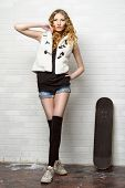 Trendy teen girl with bright foxy hair alluring with her skateboard by a brick wall. Youth fashion. poster