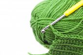 Skein of wool crochet hook and knitted piece isolated on white poster