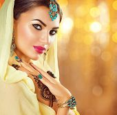 Beautiful fashion Indian woman portrait with oriental accessories- earrings, bracelets and rings. Arabic girl with black henna tattoos and beauty jewels. Hindu model with perfect make-up. India poster