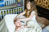 Little sister hugging her newborn brother. Toddler kid meeting new sibling. Cute girl and new born baby boy relax in a white bedroom. Family with children at home. Love trust and tenderness concept. poster