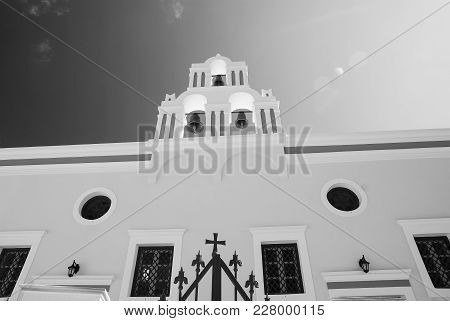 Greek Orthodox Beautiful White Church With A Bell Tower Against The Clear Blue Sky In Oia Village On