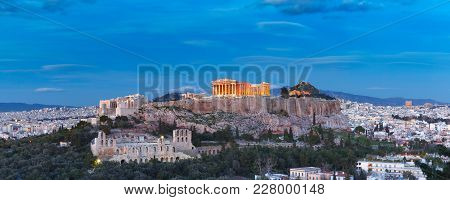 Aerial View Of The Acropolis Hill, Crowned With Parthenon, Above Of The City Skyline During Evening