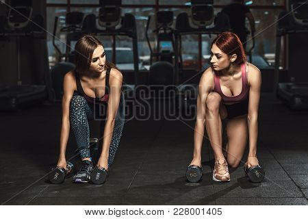 Two Beautiful Fitness Sporty Young Girls Doing Lunges With Dumbbells In Dark Gym