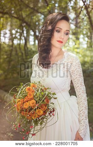 Portrait Of Young Beautiful Woman Bride In White Dress Looking Aside, Holds A Wedding Bouquet In His