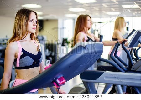 Running Together. Side View Close Up Of Young Beautiful Women Looking Away While Running On Treadmil