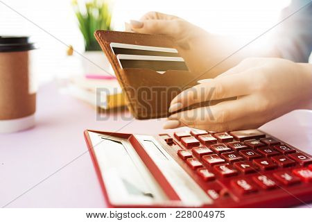 Woman Is Holding Purse, Credit Card In Hands And Calculating The Costs. Pink Table. Flowers On The T