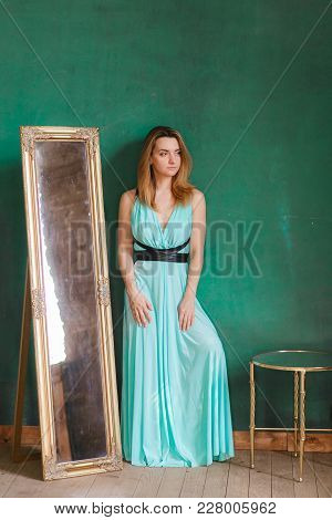 Young Beautiful Woman In Cocktail Dress Standing Near Vintage Mirror Looking Left Side. With Green E