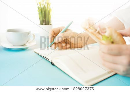 Male Hands Holding Pen, Sandwich, Writing. Side View On Man On Trendy Color Blue Desk. Man And Stili