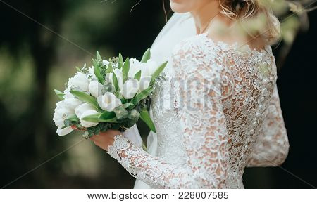 Beautiful Bouquet Of Different Colors In The Hands Of The Bride In A White Dress