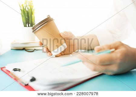 Male Hands Holding Pen, Writing. Side View On Man On Trendy Color Blue Desk. Man And Stilish Workpla