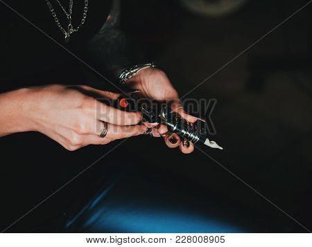Female Artist Prepares Tools And Machine For Tattoo Session, Holding A Tattoo Gun. The Tattooist Che