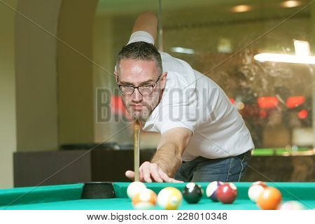 A Man Plays A Billiard At The Club. Young Man Playing Spending Time On Recreation. Play And Fun Conc