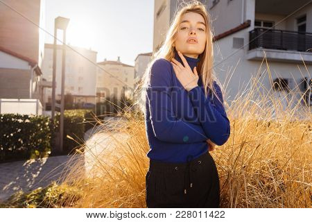 Attractive Young Blonde Girl Posing In Trendy Blue Sweater, Street Style