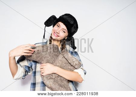 Happy Beautiful Russian Girl In Warm Hat With Ear-flaps Holds Gray Felt Boots, Smiling