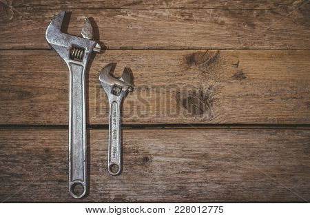 Two Wrenchs, Big And Little On Wooden Background With Copy Space. Top View.