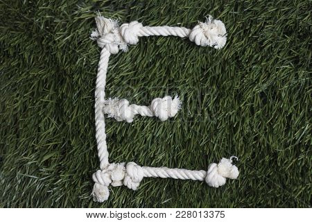 Rope Latin Alphabet On Grass. Letter E