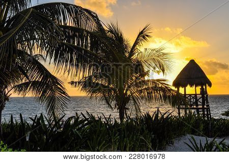 Sunrise In The Riviera Maya, Mexico, With A Lifeguard Tower And Palm Trees In The Foreground.