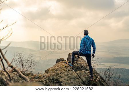 Man Celebrating Or Praying In Beautiful Inspiring Mountains Sunrise. Hiker Silhouette On Mountain To