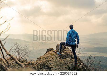 Man Celebrating Or Praying In Beautiful Inspiring Mountains Sunrise. Hiker Silhouette On Mountain To