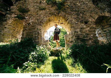 Active Young Girl Travels, Stands In An Ancient Abandoned Building Surrounded By Greenery