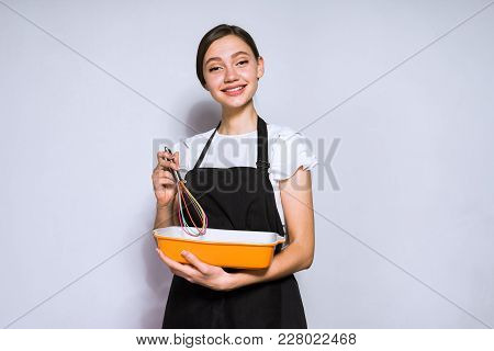 Happy Young Girl Cook In A Black Apron Preparing A Delicious Pie