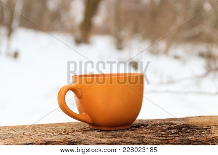 Orange Cup Of Coffee On The Background Of The Winter Forest