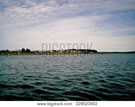 A Little Settlement Consisting Of Wooden Houses Stationed Oneself On Salient Part Of Lakeshore With