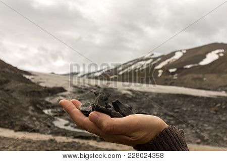 Female Hand Holding Coal Found By The Longyear Glacier. Glacier, Arctic Landscape Of Glacial Moraine