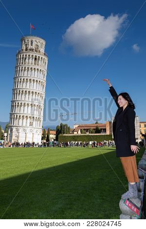Pisa, Italy - February 11, 2018: Asian Girl Poses For A Picture With The Famous Tower Of Pisa In The