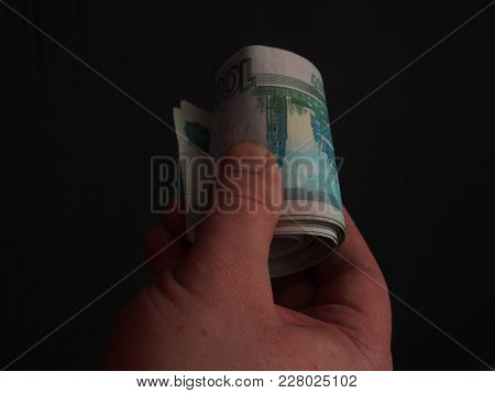 Banknotes In Denominations Of One Thousand Rubles In A Person's Hand. Money Rolled Up In A Tubule.