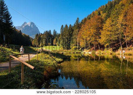 Beautiful Mountain Lake With Rock And Colorful Forest In The Background And Walking Woman