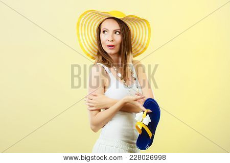 Holidays Summer Fashion Concept. Woman In Big Yellow Hat Holding Flip Flops In Hand Bright Backgroun