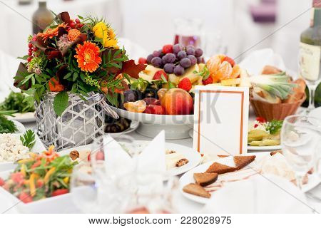A Beautifully Decorated Festive Table With A Meal In The Center Of Which Stands A Vase With A Bouque