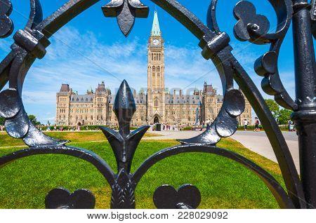 Ottawa-canada: Parliament Of Ottawa Through A Black Fence With Deep Green Grassland.