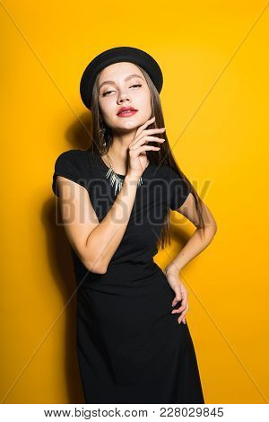 Beautiful Attractive Girl In Stylish Black Hat And Dress Posing On Yellow Background