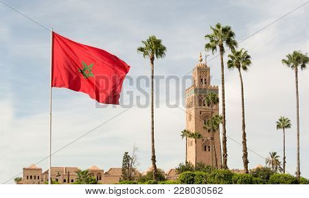 Red Flag With Palms From Morocco And Djemma El Fna Tower. Touristic Place In Marrakesh Used By Local