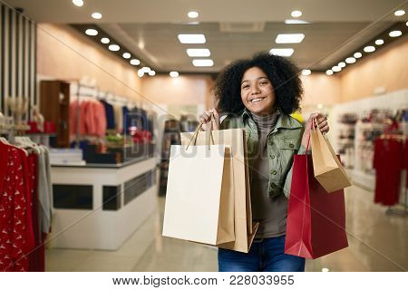 Attractive Young Cute African American Woman Posing With Shopping Bags With Clothing Store On Backgr