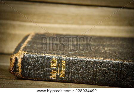 A Bible Resting On Its Side On A Wooden Table With Only The Spine In Focus With A Slight Vignette.