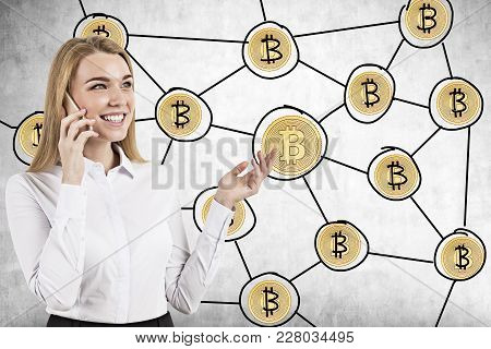 Portrait Of A Smiling Young Businesswoman Wearing A Blue Shirt And Holding A Smartphone. A Bitcoin N