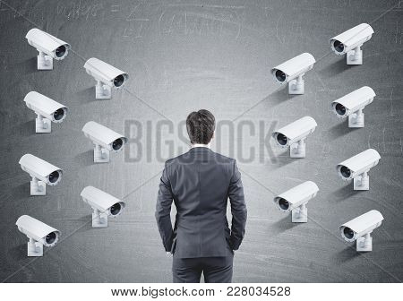 Fourteen Cctv Cameras Hanging In Rows On One Concrete Wall Facing A Businessman Looking At The Wall.
