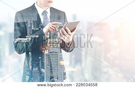 Portrait Of An Unrecognizable Young Businessman Wearing A Dark Suit With A Tie And Working With A Di