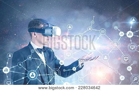 Side View Of A Fair Hair Businessman Wearing Vr Glasses, A Bow Tie And A Suit Showing A Network Holo