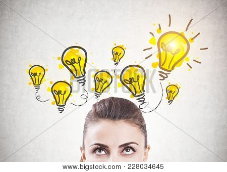 Portrait Of An Attractive Young Brunette Woman Looking Upwards At Yellow Light Bulbs On A Concrete W