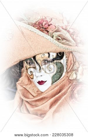 Costumed Reveler Of The Carnival Of Venice In A Pink Costume And A White Vignette.