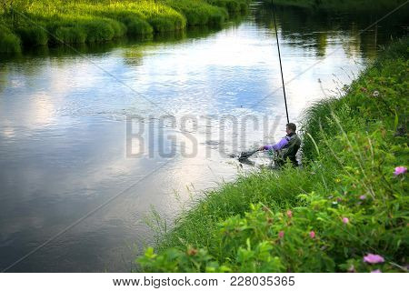 Fisherman Caught Fish On The River In The Countryside. Rural Landscape. Summer Season. Evening Time.