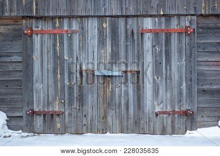 Garage Facade With Old Gray Wooden Gates. Old Garage Door